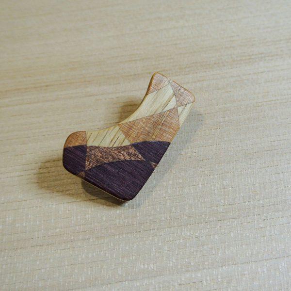 Die asymmetrische Ansteckbrosche besteht aus Amaranth, Mahagoni, Limba und Okumé.