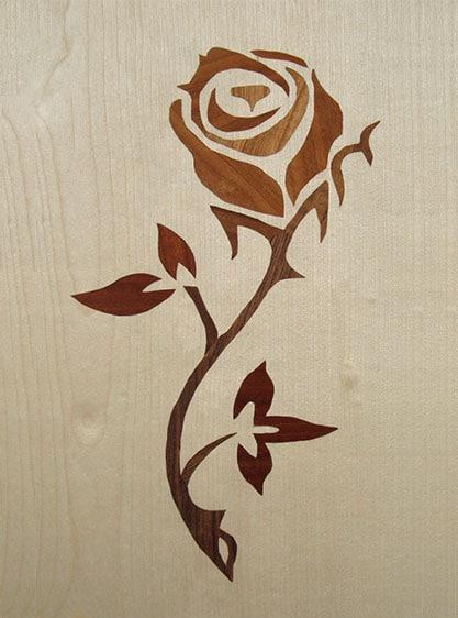 helles Bild aus Holz, in das mit dunklem Holz eine Rose eingelegt wurde