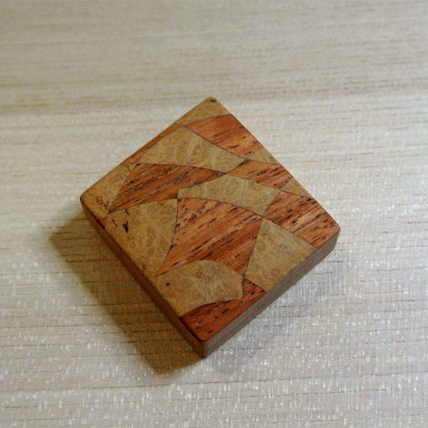 Die rechteckige Magnetbrosche mit einem Puzzle-Muster aus Sipo-Mahagoni und Myrte Maser unterstreicht Ihr persönliches Outfit.