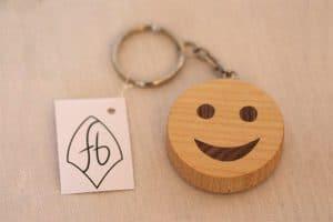 runder Schlüsselanhänger aus hellem Holz mit Smiley