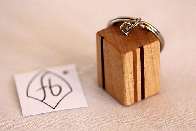 quaderförmiger Schlüsselanhänger aus Holz mit schmalen Streifen