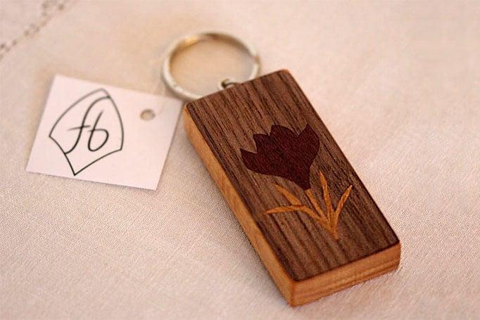 Schlüsselanhänger aus dunklem Holz mit Blumenmotiv