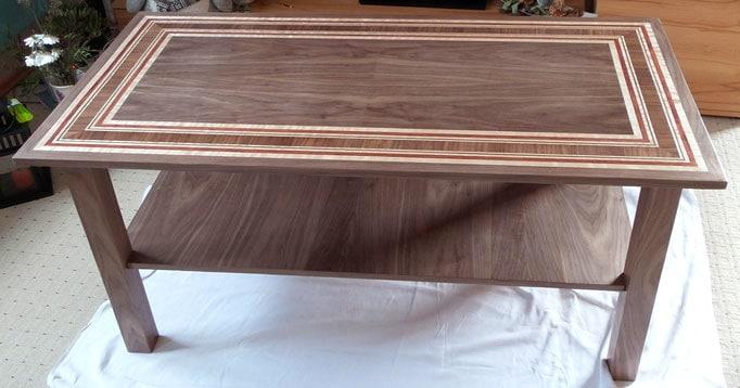 Tisch aus dunklem Holz mit Mustern aus Intarsien